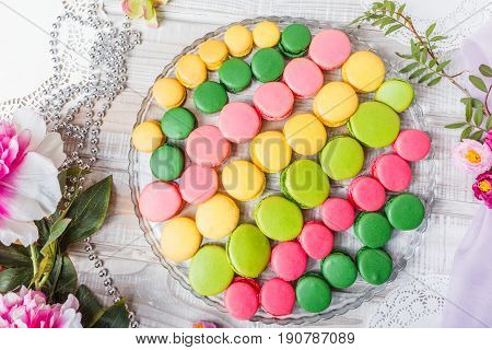 Colorful tasty macaroons on wooden table with flowers a french sweet delicacy macaroon texture. Top view flat lay