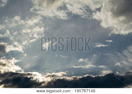 Beautiful blue sky with Cumulus clouds and dark clouds. In the middle of a clear sky with haze and visible rays of the sun. The frame is in the form of clouds. A bit of Cirrus clouds.