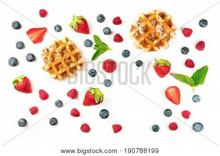 A photo of Belgian waffles with fresh fruit and mint leaves, shot from above on a white background with a place for text