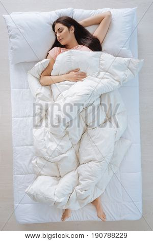 So warm. Nice young pretty woman lying on the bed and covering herself with the blanket while enjoying her sleep