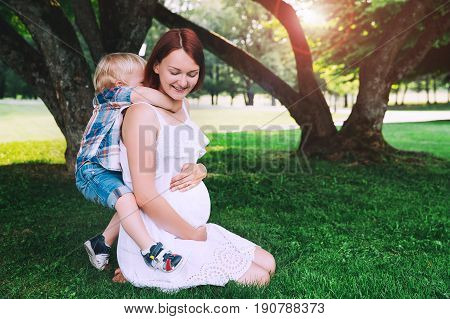 Pregnant woman with child outdoors. Mother and son on nature backgrounds in summer park. Little child boy hugging mother who pregnant for second time. Pregnancy new life family parenthood concept.