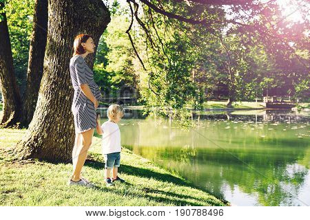 Pregnant woman with child outdoors. Mother and son on nature in summer park. Little child boy walking with mother who pregnant for second time. Pregnancy new life family parenthood concept.