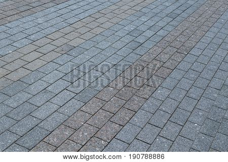 Area or walkway made of granite or marble rectangular tiles grey and brown. Tiles laid out in a line line by line. Visible streaks in the tiles.