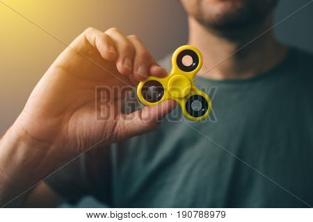 Yellow fidget spinner in male hand selective focus