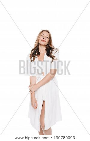 Portrait Of Cute Woman In White Robe Posing And Looking At Camera Isolated On White