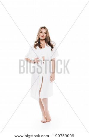 Beautiful Woman In Housecoat Standing Barefoot And Looking At Camera Isolated On White