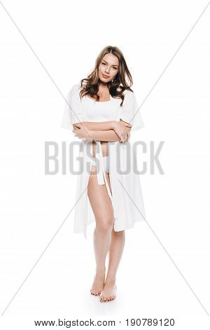 Young Woman In Housecoat Standing Barefoot And Looking At Camera Isolated On White