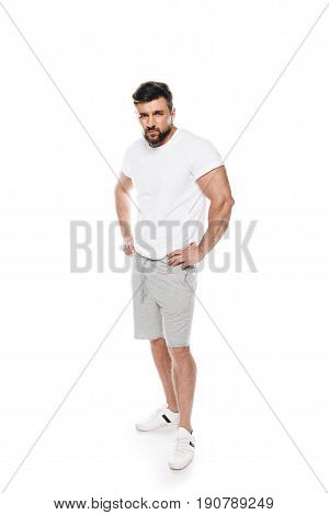 Portrait Of Confident Muscular Man Posing In Casual Clothes And Looking At Camera Isolated On White