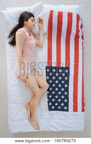 American nation. Nice pretty young woman lying on the bed near the US flag and sleeping while being a US patriot