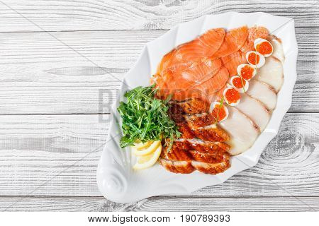 Seafood platter with salmon slice smoke sturgeon quail eggs with red caviar slices fish fillet decorated with arugula and lemon on wooden background close up. Mediterranean appetizers. Top view