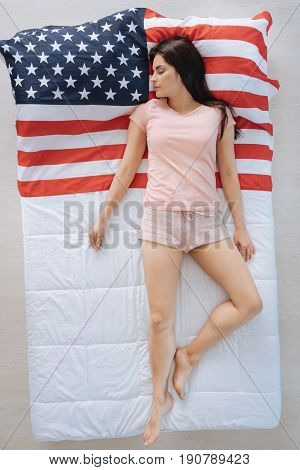 Great nation. Peaceful nice young woman lying on the American flag and sleeping while being a patriot of her country