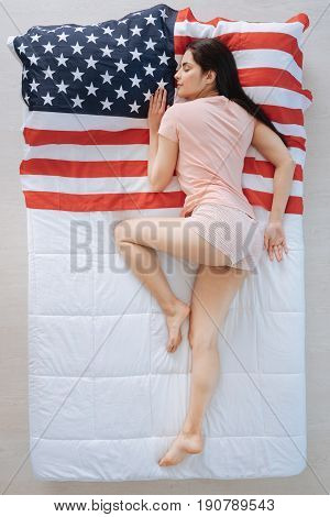 Nationalistic feelings. Joyful nice pleasant woman lying on American flag and having a nap while expressing her patriotic feelings