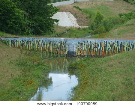 This is ditch art. A  underground water pipe  resurfaces on either side of a drainage canal. The support concrete was quickly made less noticeable with the painting on the support base.