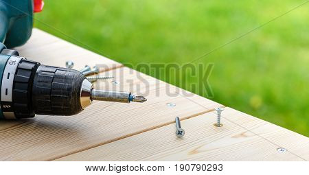 Screw being screwed into a wooden board by electric screwdriver on green outdoor background