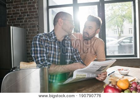 Happy Homosexual Couple Sitting At Table And Reading Newspaper At Morning