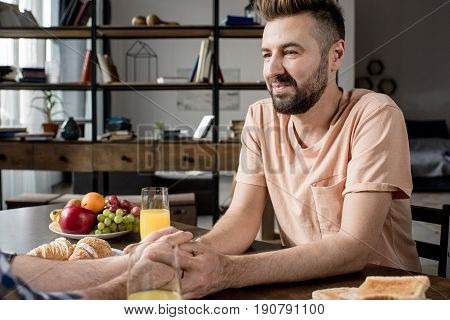 Cropped shot of homosexual couple holding hands while sitting at table with fruits and juice in glasses