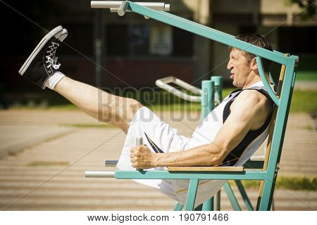 The athlete is exercising abdomen on the gym outdoors.
