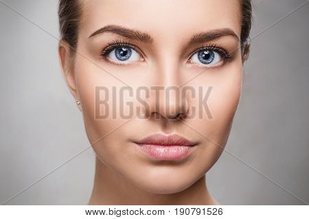 Beautiful face of young woman with perfect skin and makeup. Fresh skin close-up over gray background. Beauty Portrait.