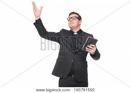 Young Priest In Black Suit Holding Scripture Book With Hand Gesture Isolated On White