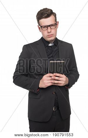 Young Priest In Black Suit Holding Scripture Book And Looking At Camera Isolated On White