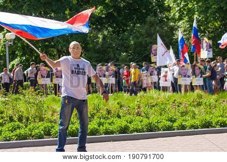 A Masked Man And A Flag At A Rally At A Rally Against Corruption In The City Of Cheboksary, The Chuv