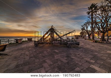 Antique catapult on a colorful sunset in Alghero. Sardinia Italy