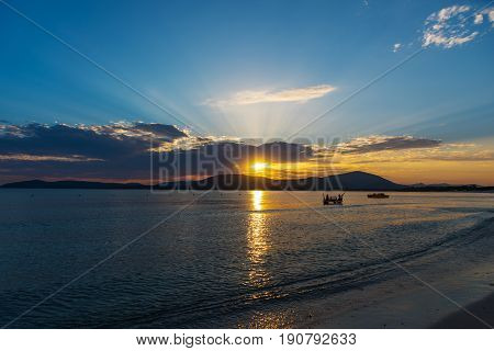 Shining sun and dark clouds in Alghero at sunset. Sardinia Italy
