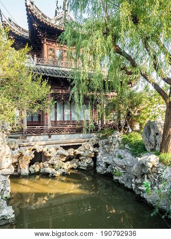 Shanghai, China - Nov 4, 2016: In Yu Yuan (Yu Garden) - A tranquil traditional Chinese architectural scene, featuring landscaped trees, rockery, pond with carps, and bush.
