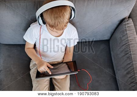 Child on the new era. Diligent motivated clever boy wearing headphones while watching videos on his gadget and sitting on a sofa