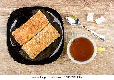 Flaky Cookies In Plate, Tea, Spoon And Lumpy Sugar