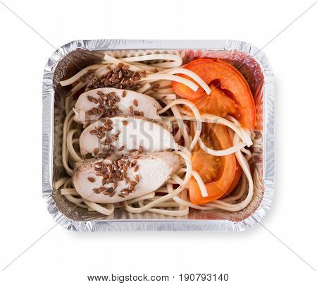 Healthy lunch in foil container. Healthy food take away and delivery. Durum wheat pasta, steamed turkey, fresh vegetables and flax seeds in box on white background, closeup, isolated
