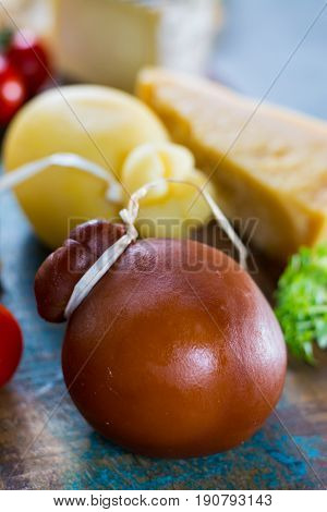 Traditional Italian hard cheese Provolone of Caciocavallo smoked and white on wooden background