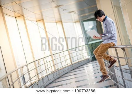 Young Asian casual business man sitting on railing in corridor space and using laptop computer digital nomad lifestyle concept
