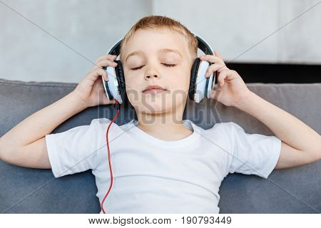 Relaxing songs. Artistic thoughtful passionate kid sitting on a couch and wearing headphones while enjoying sounds of his playlist