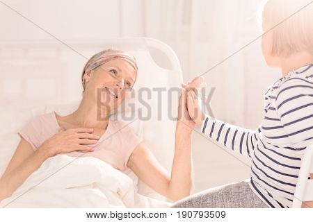Mother after chemotherapy in bed touching her daughter