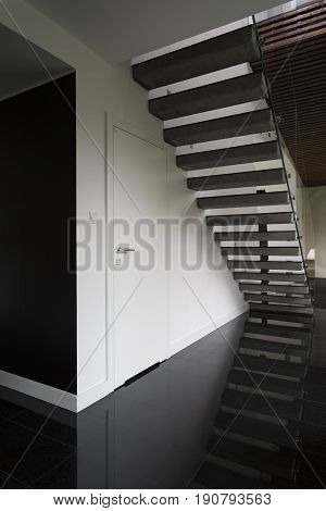 Spacious black and white hallway with stylish stairs