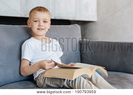 Little scientist. Admirable persistent excited boy sitting in a living room and reading something interesting while enjoying his free time at home