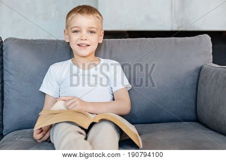 Mature leisure. Intelligent ambitious gifted boy loving fantastic stories and enjoying reading a book while sitting on a cozy sofa