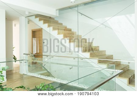 View of modern bright corridor with minimalistic wooden stairs with glazed handrail