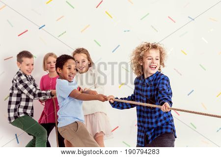 Group of young sweet kids pulling a rope