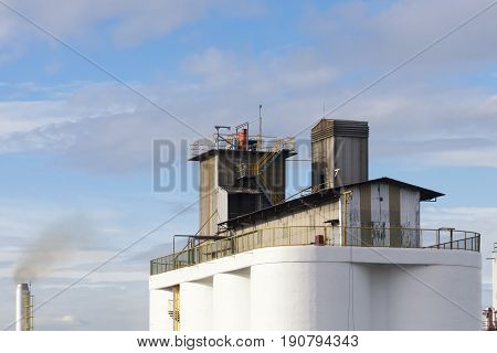 The factory building and the smoke stack with the blue sky.Industrial building