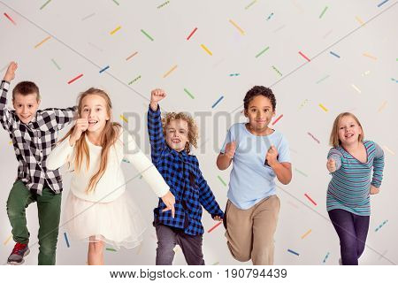 Group of young happy friends running ahead