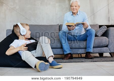 Different but same. Nice young savvy kid using gadget for reading while his grandpa preferring real books