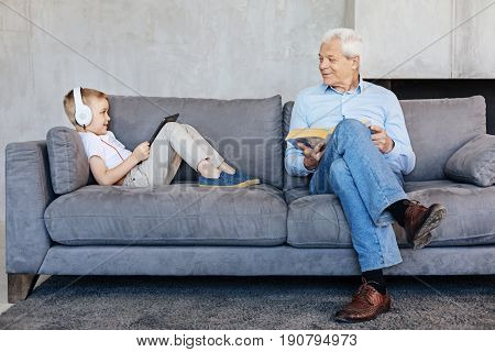 Two generations. Active savvy original kid using tablet for watching informative videos while his grandpa preferring reading books