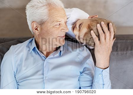 Looking at the future. Adorable wise elderly man talking to his grandson while he wanting playing with his grandpa and asking him if he agreeing