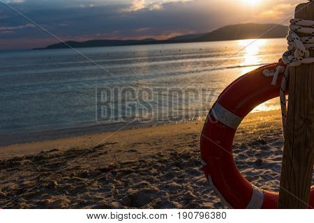 Life buoy by the shore at sunset. Alghero Italy