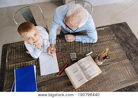 Like a professor. Inventive smart cute boy sitting at the table and working on home assignment while his grandpa explaining him some basic rules