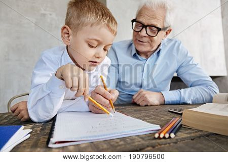 Numbers are easy. Wise educated mature man explaining his grandson some rules while helping him fulfilling his home assignment