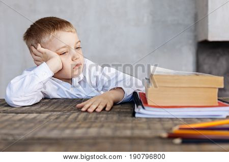 Just too much. Weary sad cute boy sitting at the table and looking at the pile of book while deciding whether or not making his home assignment
