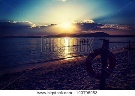 Life buoy by the sea at a scenic sunset. Sardinia Italy